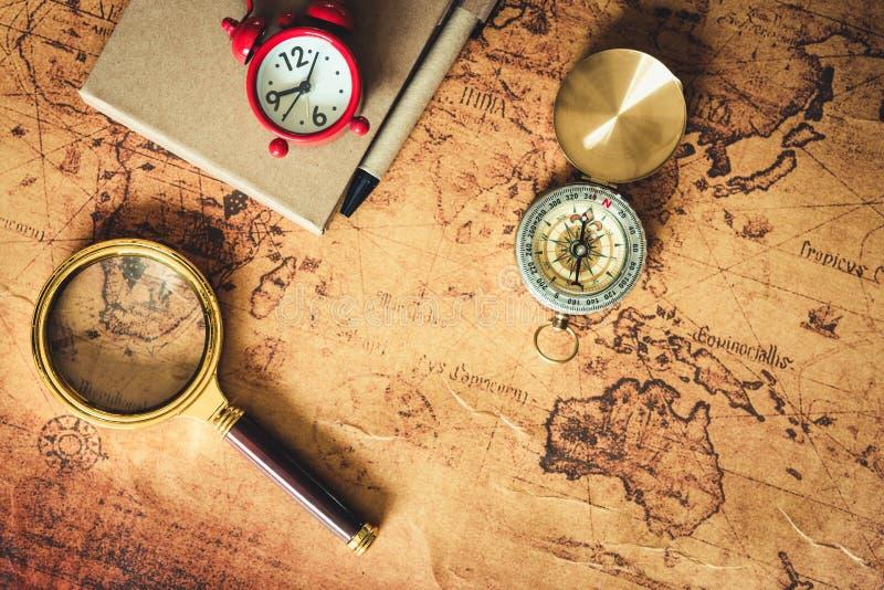 Navigering undersöker resaplanläggning med kompassförstoringsglas- och rovaorienteringen på världskartabakgrund , Expeditioner royaltyfria foton