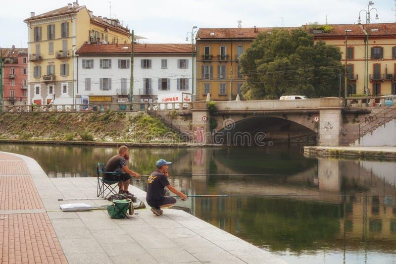 Naviglidistrict en de kanalen van Milaan in de zomer De vissers vangen vissen stock foto's