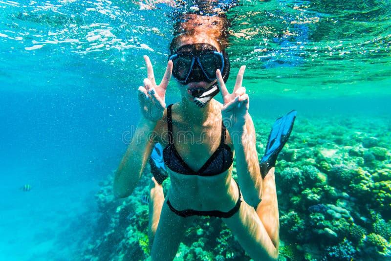 Naviguer au schnorchel sous-marin de femme avec la natation heureuse de signe de victoire en mer photos libres de droits