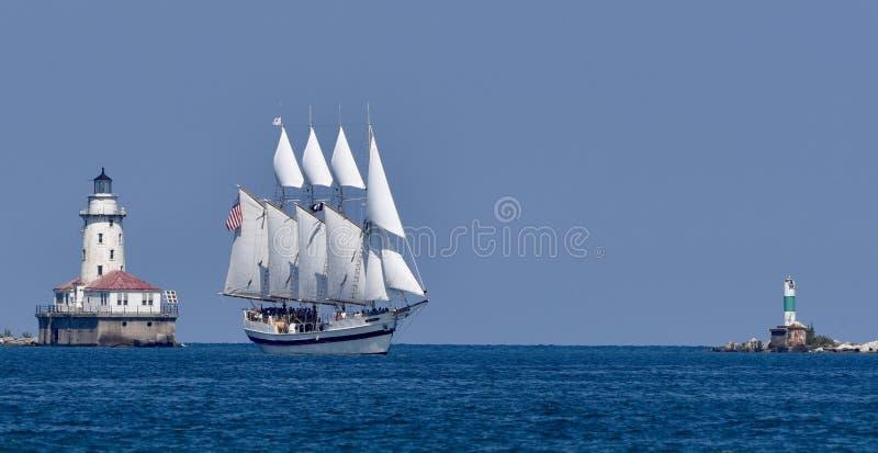 Navio alto que passa o farol do porto de Chicago fotografia de stock royalty free