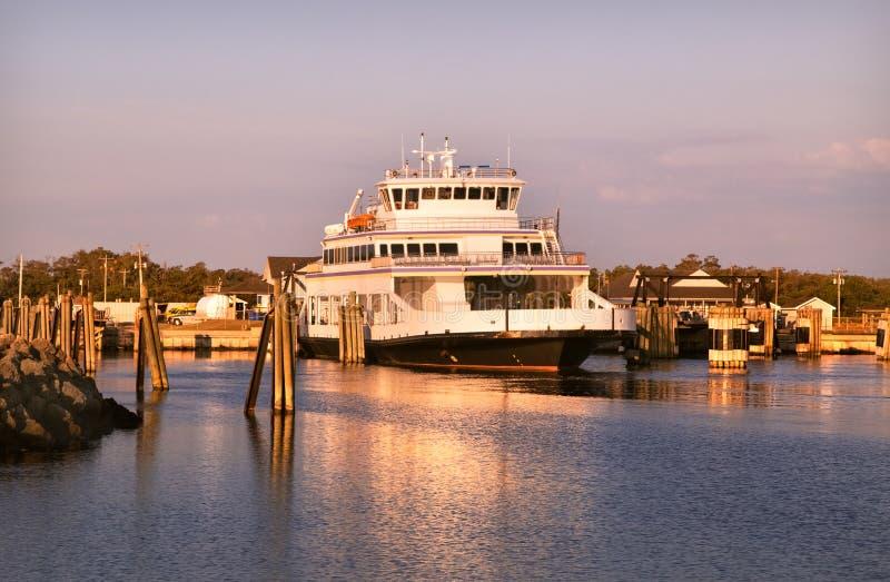 Navio da balsa, polos de madeira Oceano Atlântico NC EUA Céu das nuvens do rosa da elevação de Sun foto de stock royalty free