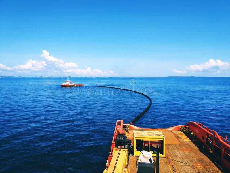 Navio de abastecimento de rebocadores ao largo que transporta uma explosão de derramamento de petróleo para exercício de derramam imagem de stock royalty free