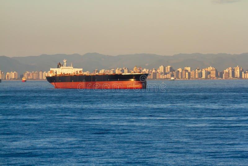 Navio de carga gigante da maioria longe no achorage com a cidade bonita no fundo fotos de stock royalty free