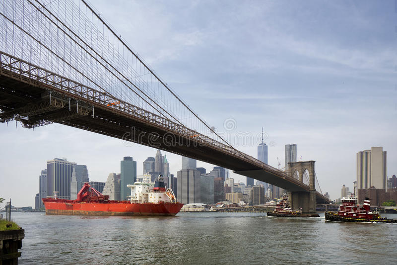 Navio de carga sob a ponte de Brooklyn, New York City foto de stock royalty free