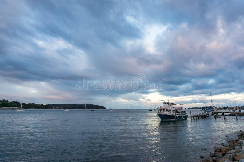 Navio de cruzeiros, barco na baía de Batemans com o céu dramático do por do sol no fundo fotografia de stock