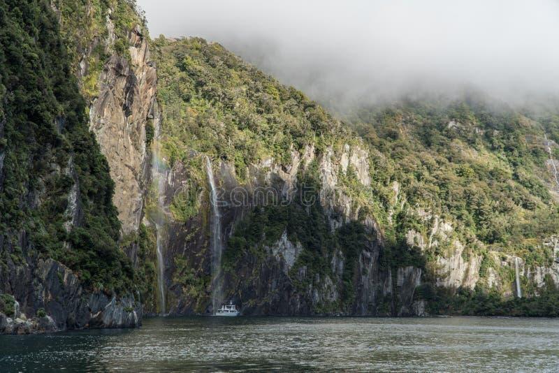 Navio de cruzeiros em Milford Sound abaixo da cachoeira em Nova Zelândia fotos de stock