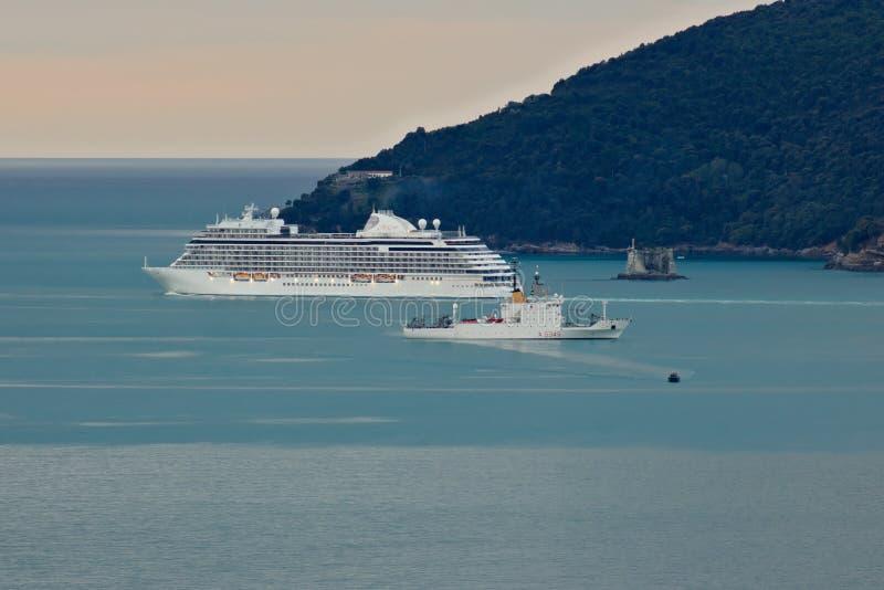Navio de cruzeiros de Regent Seven Seas Explorer e o navio militar Alliance imagens de stock royalty free