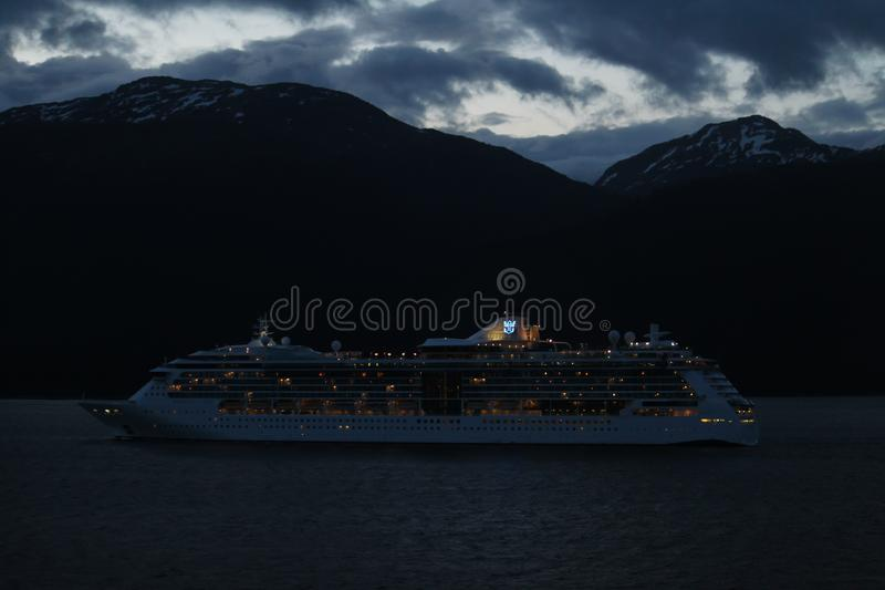 Navio de cruzeiros de Royal Caribbean na noite que cruza ao longo do Alaskian Mountians imagens de stock royalty free