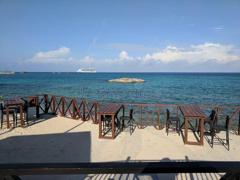 Navio de cruzeiros visto do café vazio da barra da praia fotos de stock
