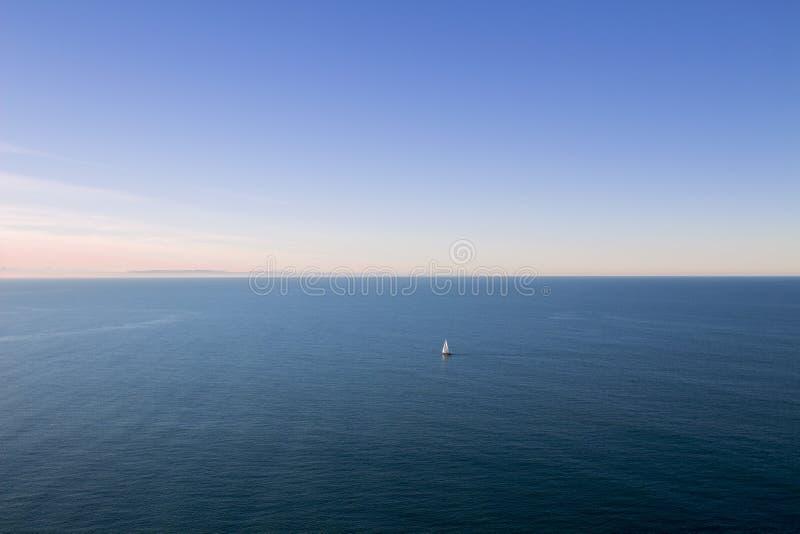 Navio de navigação que deriva durante o por do sol fotos de stock royalty free
