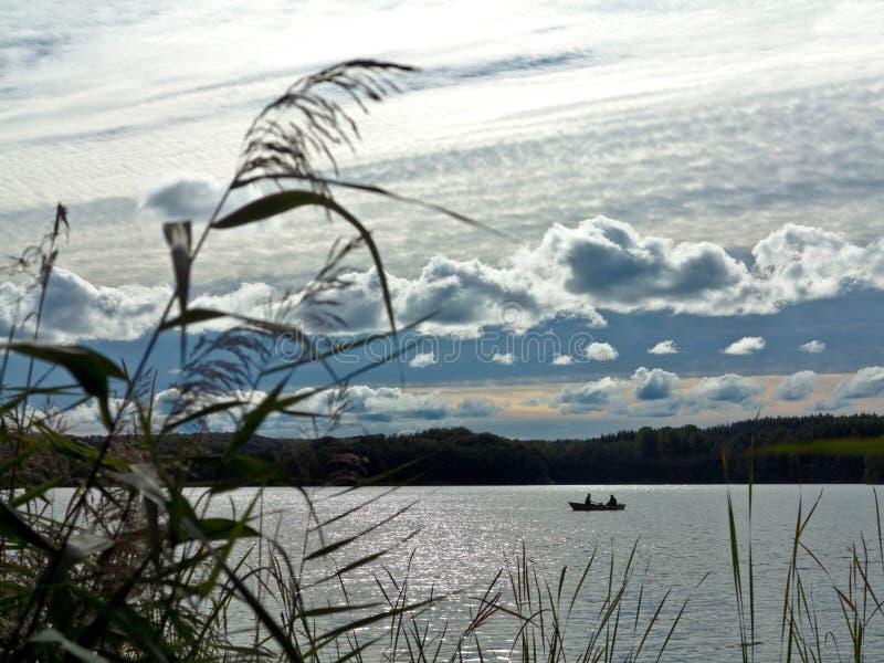 Navio de pesca com dois anjos num belo lago durante o pôr do sol imagens de stock royalty free