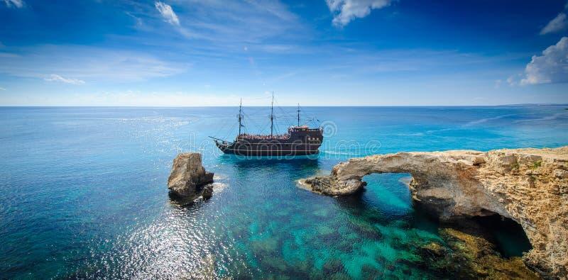 Navio de pirata pelo arco da rocha, Chipre foto de stock