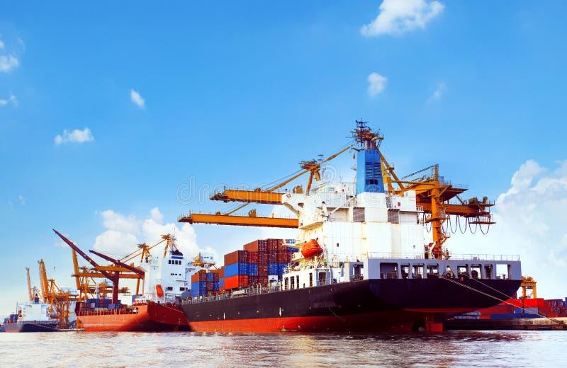 Navio de recipiente na doca da carga do porto com uso da ferramenta do guindaste dos cais para foto de stock