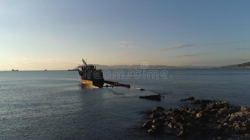 Navio destruído oxidado afundado em um mar azul no céu azul, nebuloso e no fundo de brilho do sol tiro Barco deixado de funcionar fotos de stock