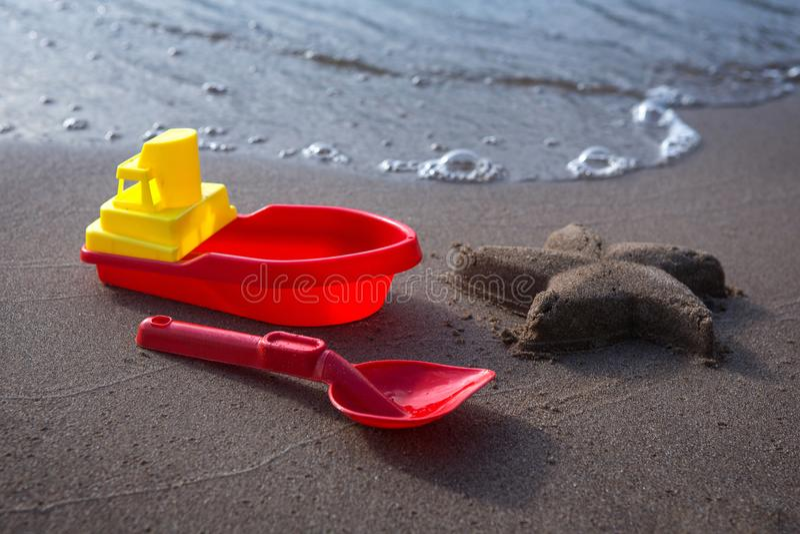 Navio e colher - os brinquedos e a estrela do mar das crianças fizeram da areia Sandy Beach, dia ensolarado imagens de stock royalty free