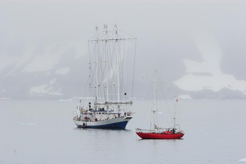 Navio grande e iate pequeno no fjord ártico fotografia de stock royalty free