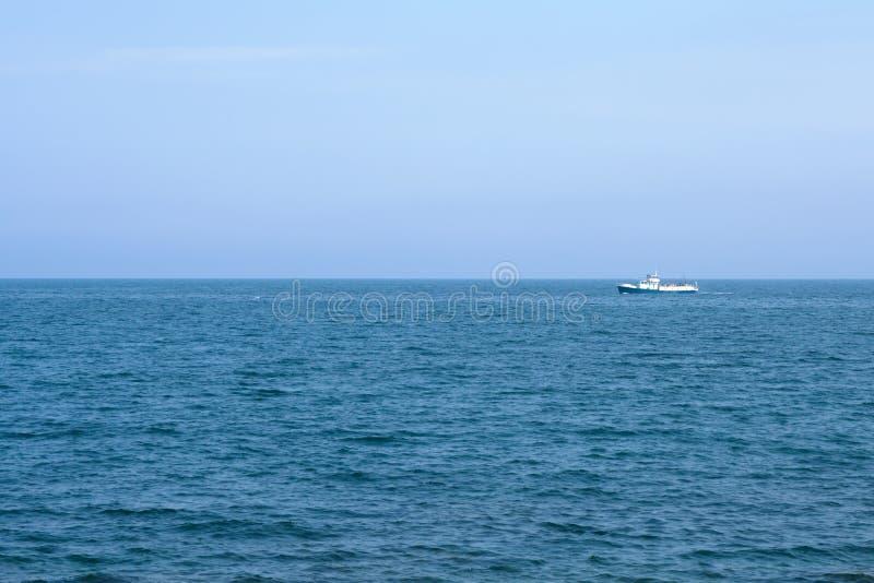 Navio no horizonte de mar azul fotografia de stock royalty free
