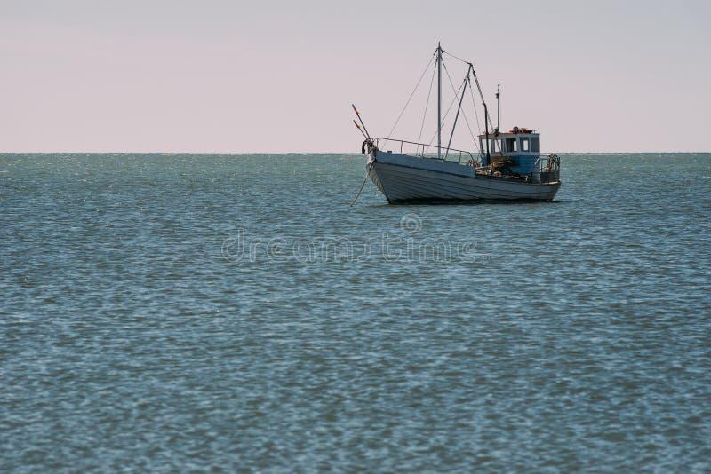 Navio pequeno da pesca na âncora na água azul imagens de stock