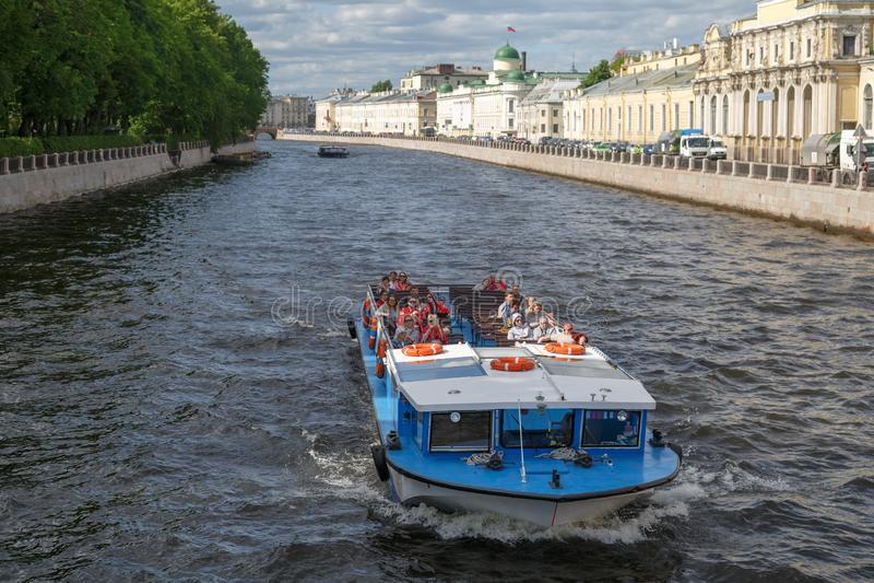 Navio sightseeing pequeno com os turistas que navegam ao longo do rio de Fontanka no centro de St Petersburg fotos de stock royalty free
