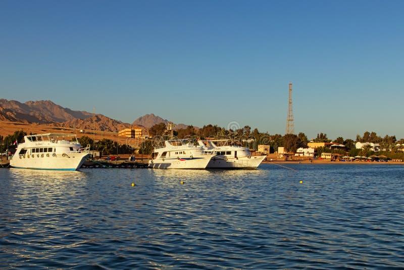 Navios de cruzeiros brancos amarrados no porto em Dahab Paisagem do Mar Vermelho com litoral e as montanhas bonitos no fundo fotografia de stock royalty free