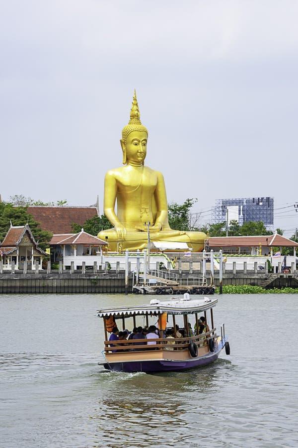 Navios que cruzam-se em Chao Phraya River e no céu e em nuvens dourados do fundo da Buda grande em Wat Bang Chak em Nonthaburi, T fotos de stock