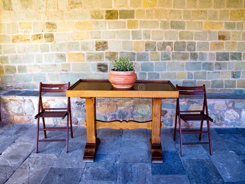 Navire antique de terre cuite en céramique avec les supports de fleur verts au milieu d'une table en bois rectangulaire photo stock