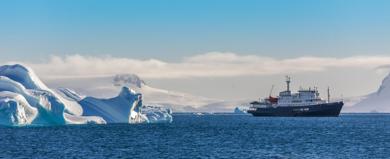 Navire bleu de croisière parmi les icebergs avec le glacier à l'arrière-plan photographie stock libre de droits