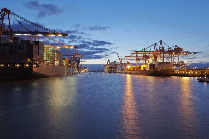 Navire de récipient sur le terminal dans le port le soir photo stock