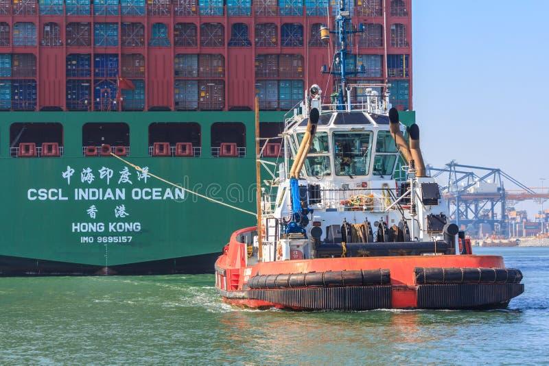 Navire porte-conteneurs avec le bateau de traction subite dans le port de Rotterdam image libre de droits