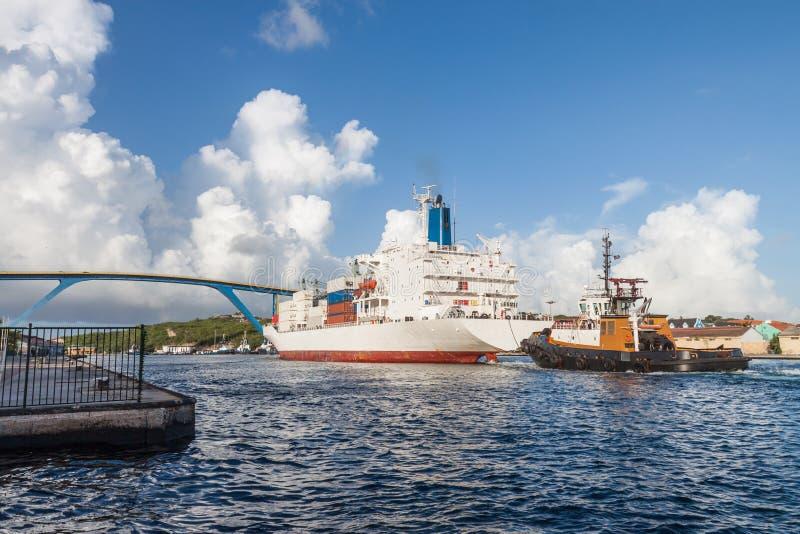 Navire porte-conteneurs et port entrant de remorqueur images stock