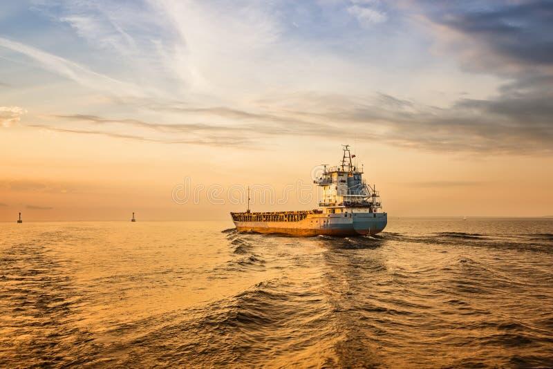 Navire porte-conteneurs sur la route de mer pendant le coucher du soleil. images stock