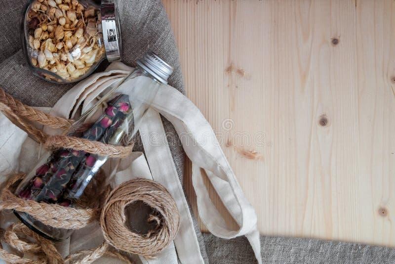 Navires en verre avec le thé, le fil de ficelle, et le mensonge floraux de sac d'eco sur un tissu de toile rugueux et un conseil  image stock