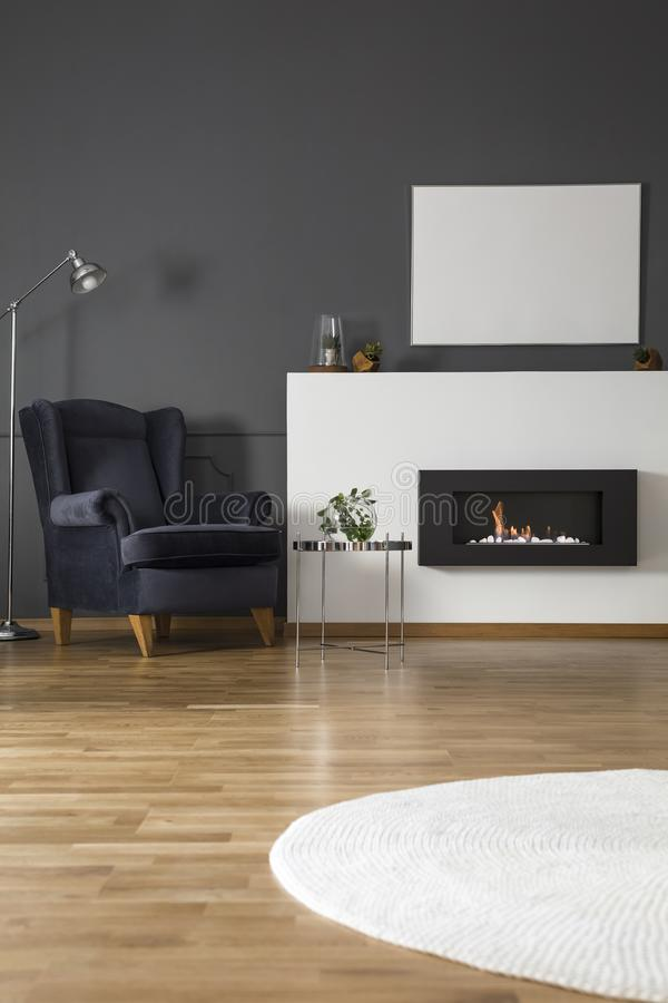 Navy blue armchair between lamp and silver table in apartment in stock photos