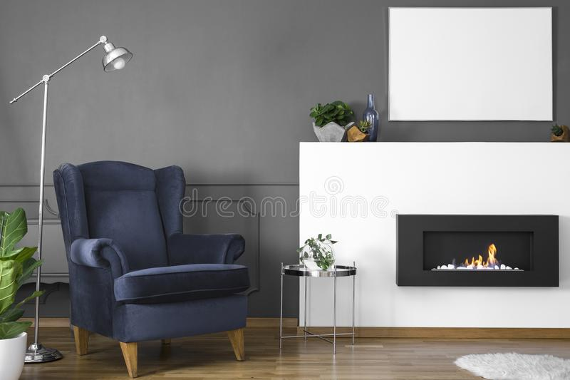 Navy blue armchair between lamp and silver table in living room royalty free stock images