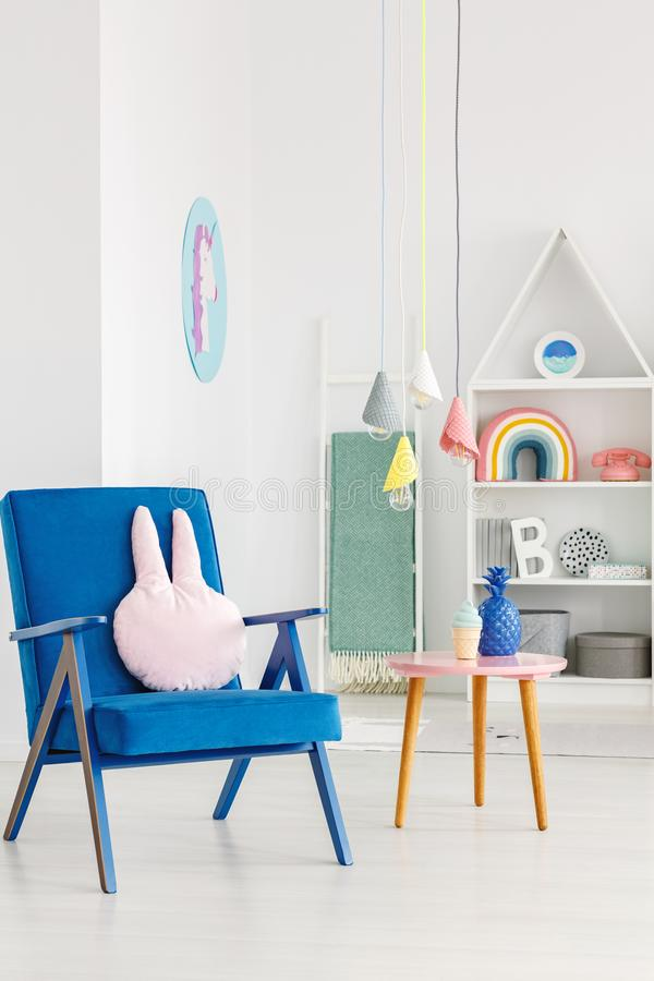 Navy blue armchair with a rabbit pillow next to a table and whit. E shelves in the background in a kid`s room interior royalty free stock images
