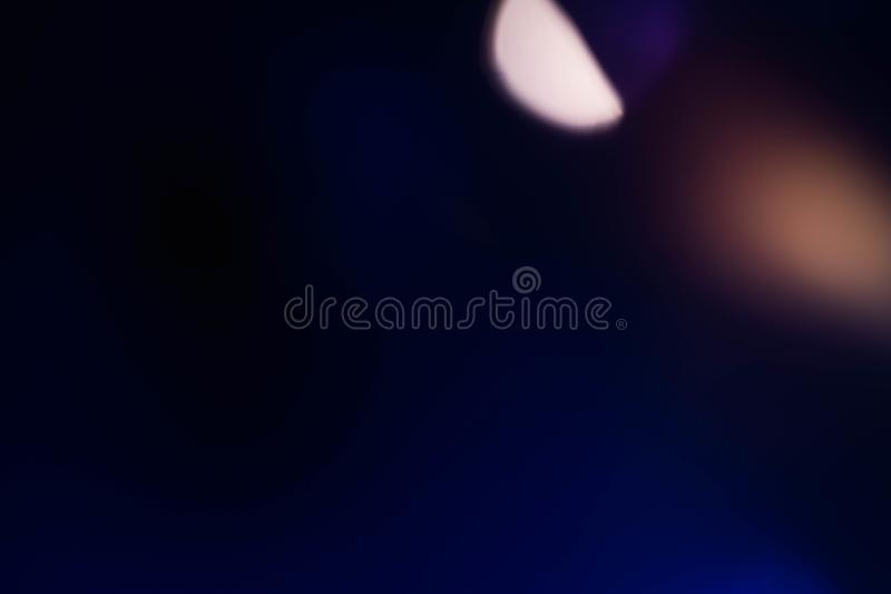 Navy blue background lens flare blur night lights. Defocused navy blue abstract art background. Colored lens flare. Blur ight lights effect royalty free stock photography