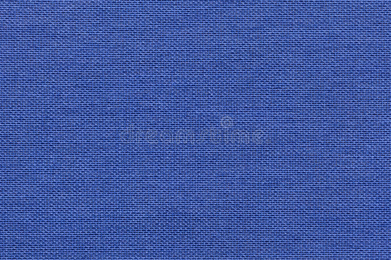 Navy blue background from a textile material with wicker pattern, closeup. Structure of the denim fabric with natural texture. Cloth backdrop stock photo