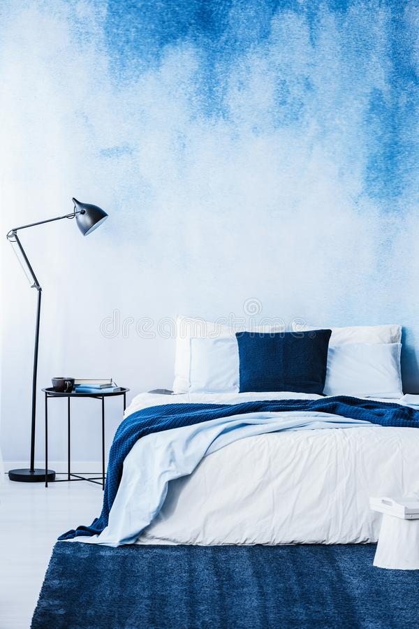 Navy blue carpet in front of bed next to lamp in bedroom interior with wallpaper stock image