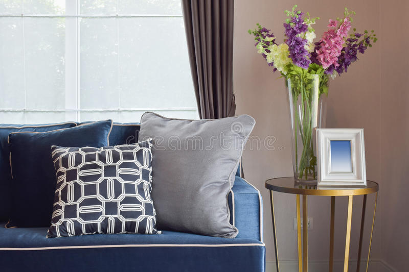 Navy blue modern classic sofa and retro, gray and blue pillows with a lovely orchid vase. On side table in living corner royalty free stock photo