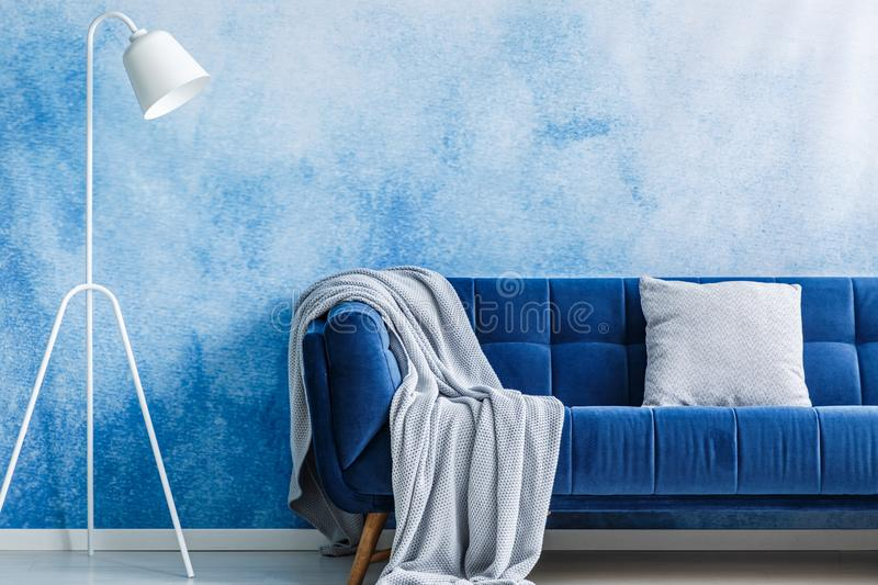 Navy blue sofa with blanket and pillow, lamp set on an ombre wall in a living room interior royalty free stock images