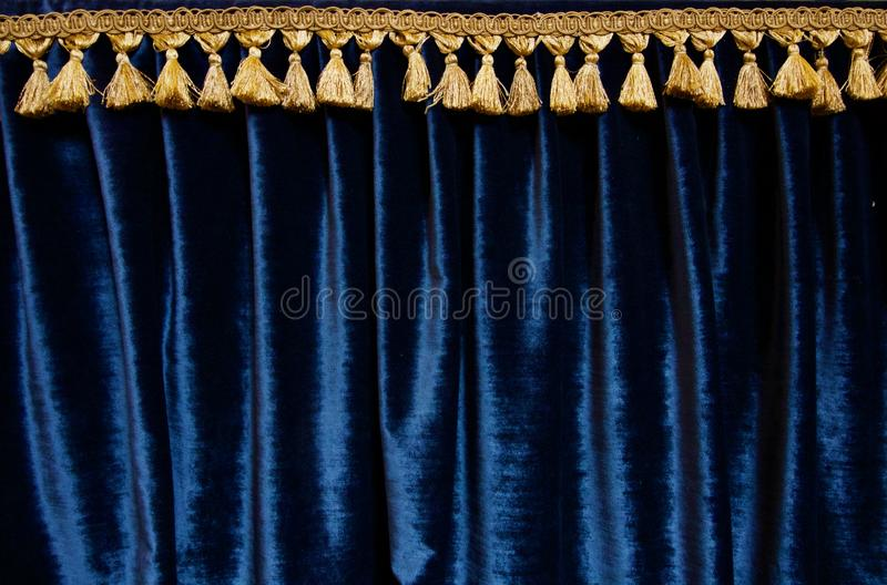 Navy blue velvet curtain with gold brocade fringe at top - image stock images