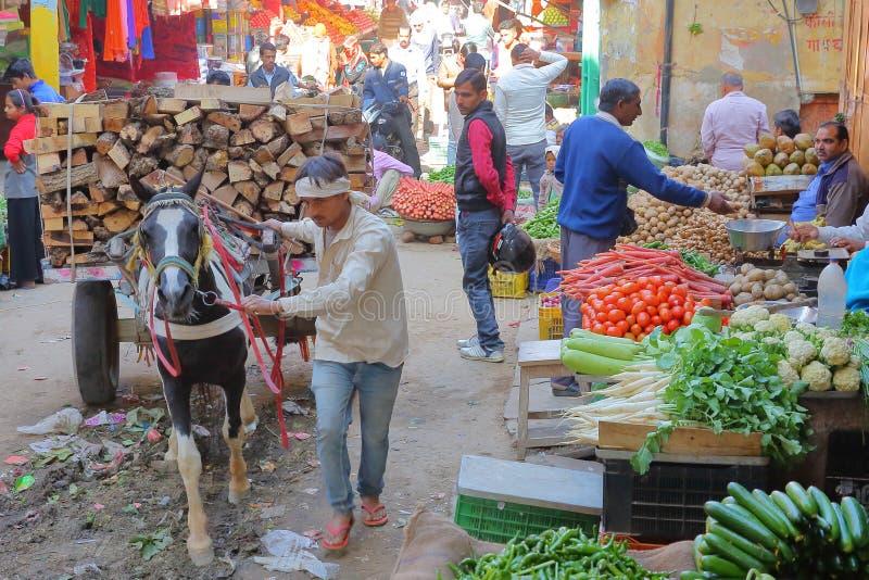 NAWALGARH, RAJASTHAN, INDIA - DECEMBER 26, 2017: De kleurrijke straatscène bij de plantaardige die markt met een vervoer wordt ov stock afbeeldingen