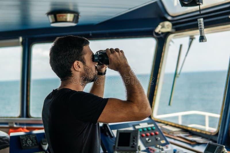 Nawigacyjny oficera punkt obserwacyjny na nawigacja zegarku patrzeje przez lornetek fotografia royalty free