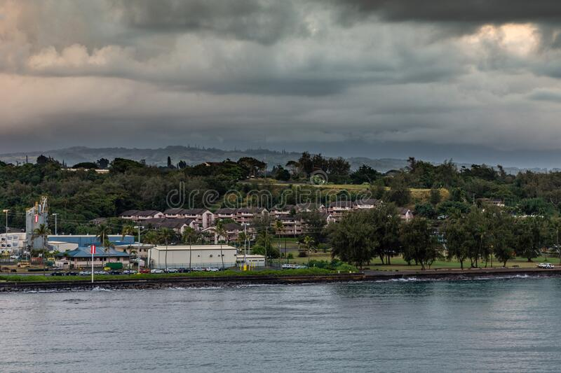 Town park with houses and part of port at Nawiliwili, Kauai, Hawaii, USA. Nawiliwili, Kauai, Hawaii, USA. - January 11, 2012: Early morning dark rainy cloudscape royalty free stock image