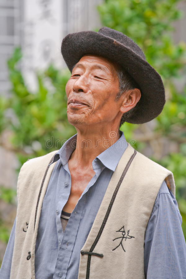 Naxi minority male singer performs in a garden, Lijiang, China royalty free stock photography