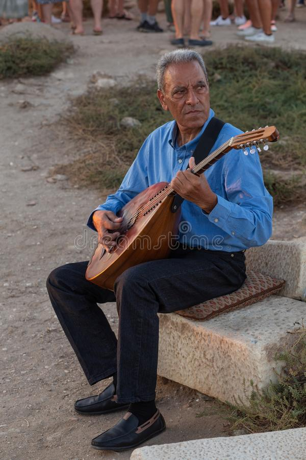 Naxos island, Greece, July 26th 2019: local man playing lte stock photos