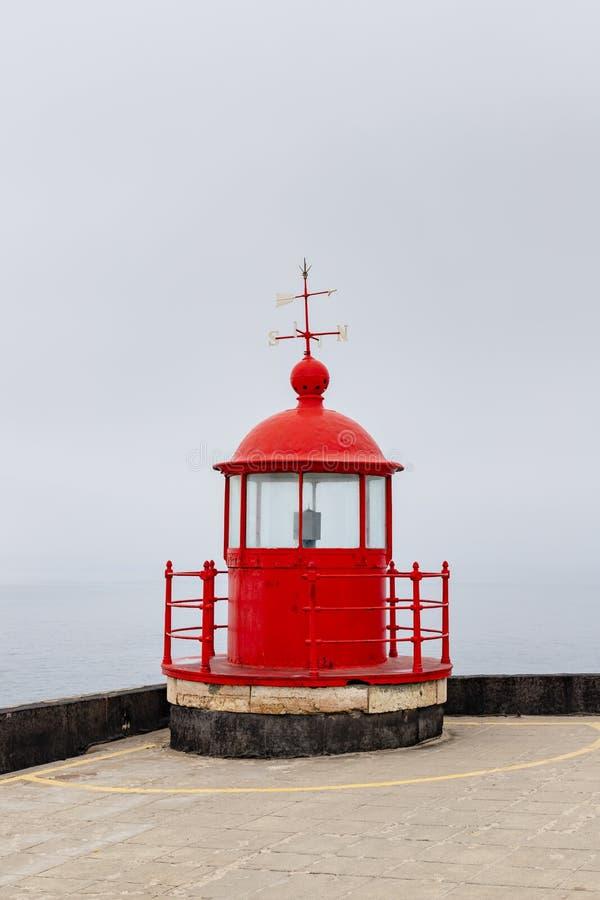Nazare,葡萄牙-在Farol顶部的红色灯塔矿灯房在薄雾 免版税图库摄影