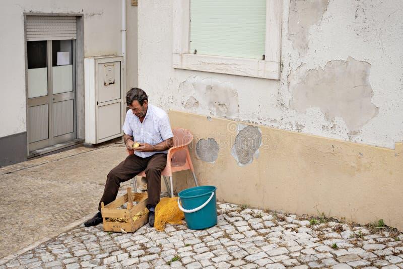 Nazare, Portugal - Juli 19, 2019: Een restaurantwerknemer zit buiten in de straten van Sitio-schilaardappels royalty-vrije stock afbeelding