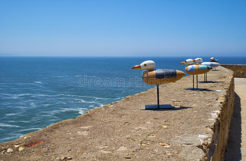 Installation art of seagulls seating on the parapet of Nazare L royalty free stock image