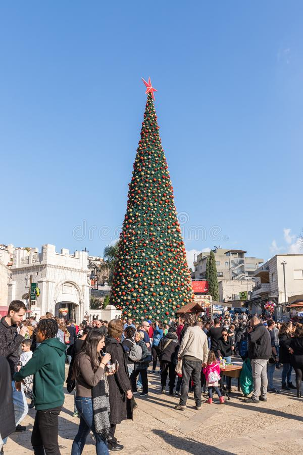 Numerous tourists walk around the square near the Christmas tree in Nazareth city in Israel royalty free stock photography